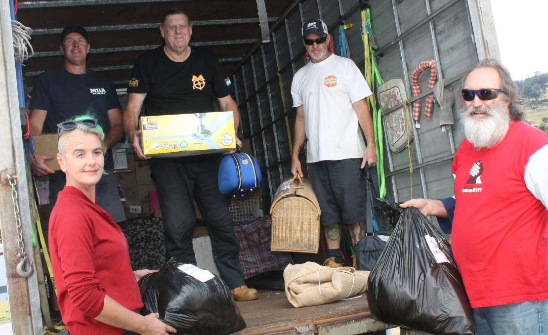 Danielle Murphy, Tony Olsson, Guy Wernhard, John Burgess and Andrew Olsson help unload the truck of donated goods at the Cobargo relief centre on Wednesday.