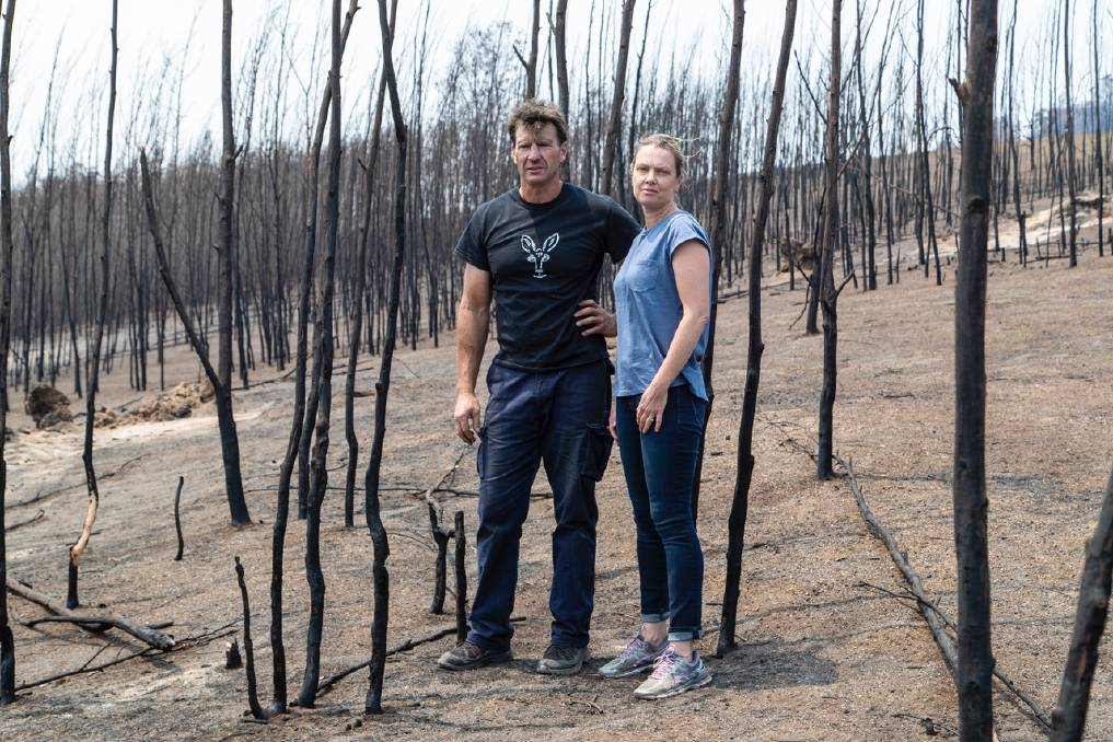 Wiped out: Gary Henderson and Sara Tilling inspect the devastated remnants of bushland that surrounded their Cobargo wildlife sanctuary. Photo: supplied.
